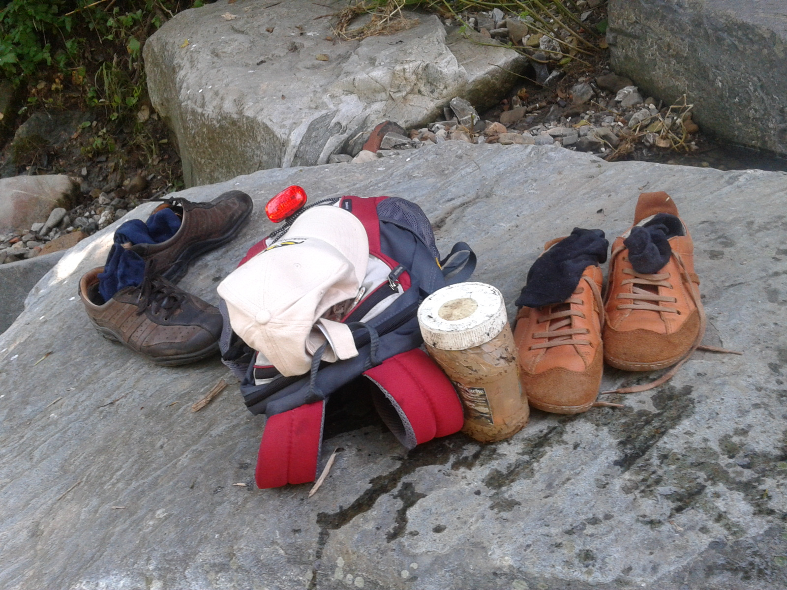 A backpack, baseball cap, 2 pairs of shoes, and a geocache container sitting on a rock.