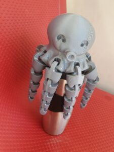 A grey, 3d-printed octopus sitting atop a thermos cup on a red seat.