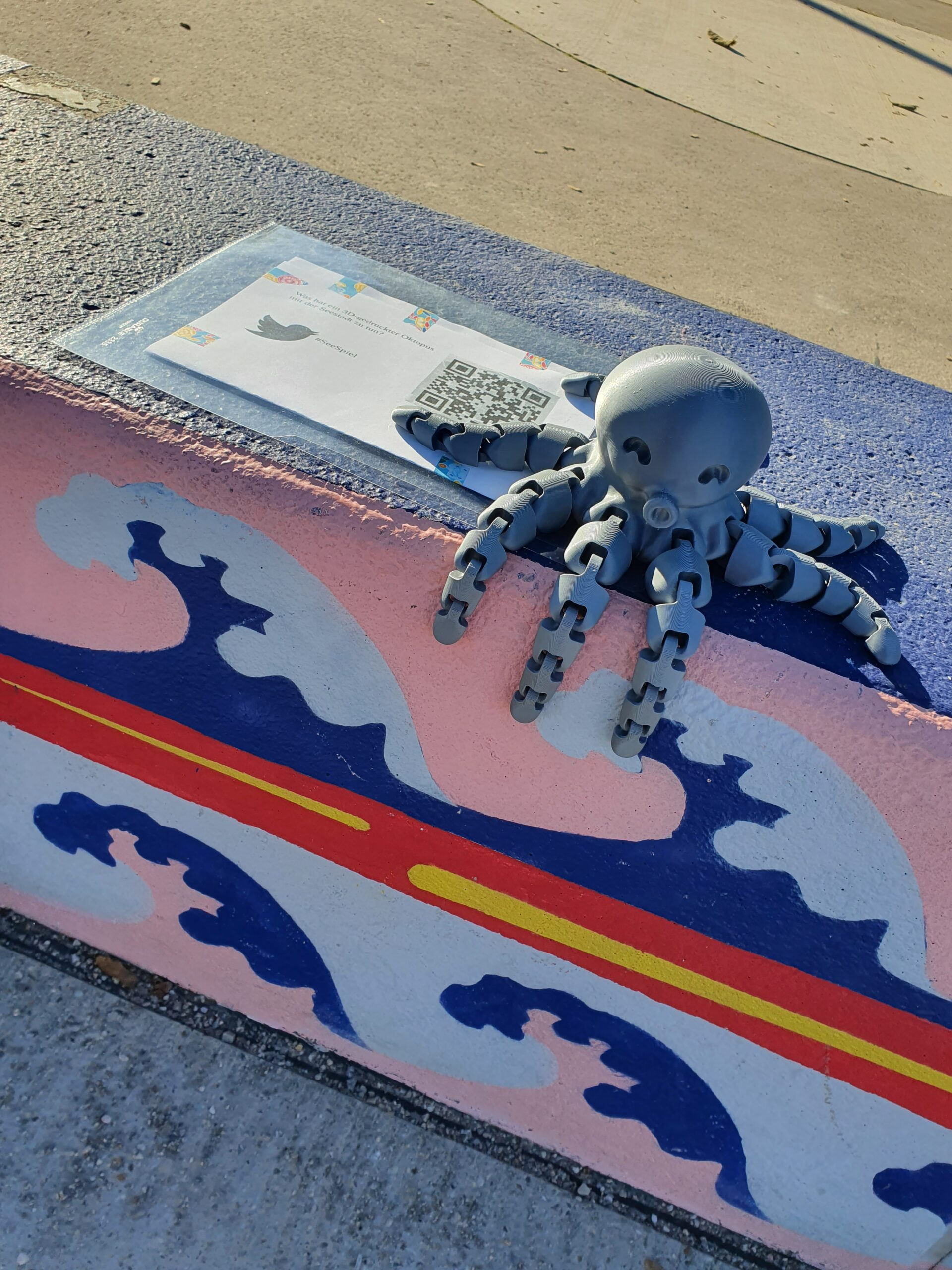 A grey, 3d-printed octopus sitting atop a wall on which waves are painted.