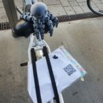 A gray 3d-printed octopus sitting atop a rental bike.