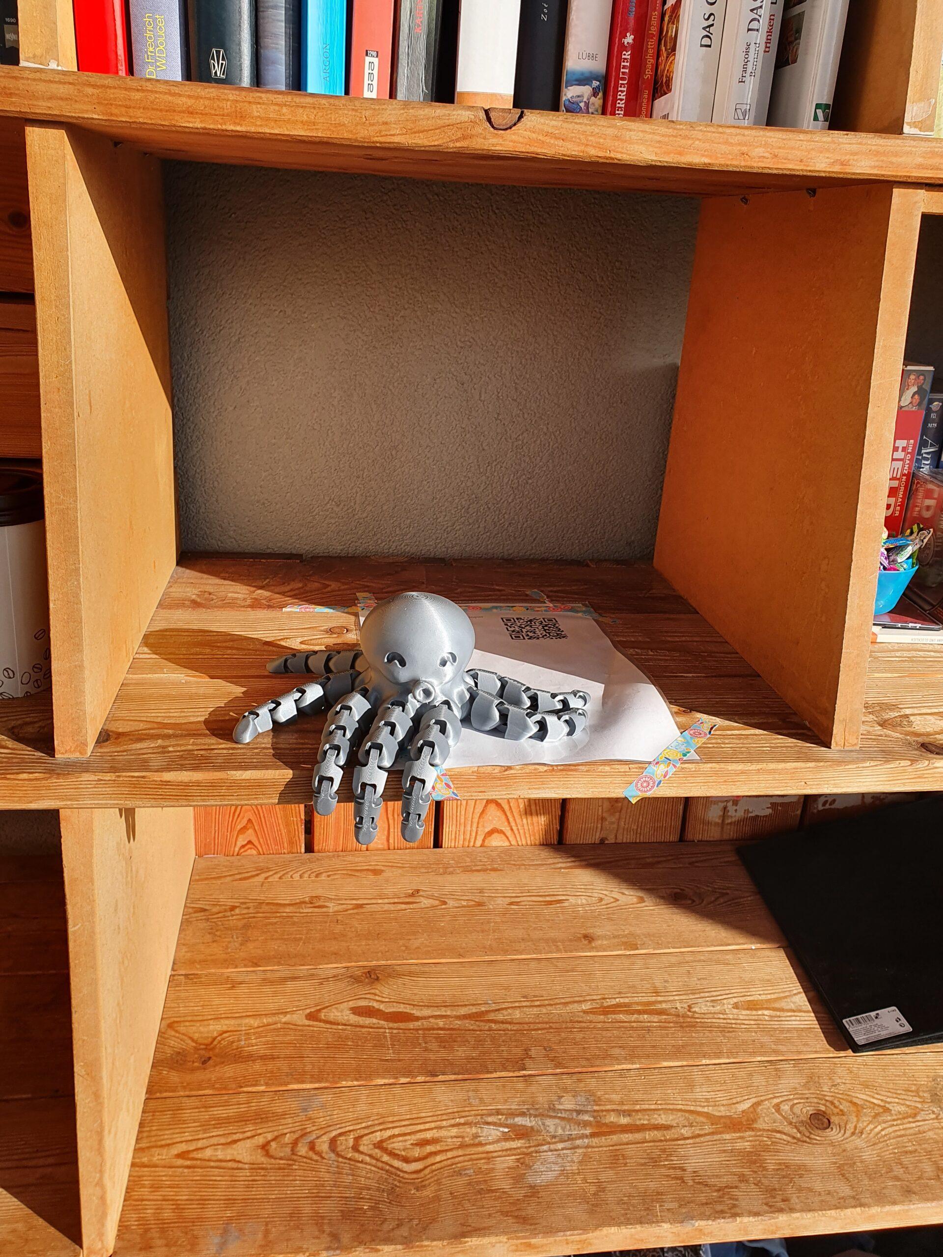A gray 3d-printed octopus sitting inside a wooden shelf.